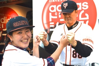 Baseball fan Risa Abe fist-pumps with a model figure outside the Tokyo Dome.